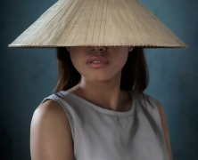 Vietnamese girl wearing non la conical hat by Adam Robert Young