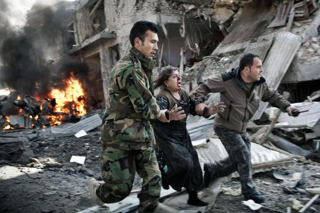 Soldiers pull a woman from the scene of a suicide car bombing in Kabul, Afghanistan.