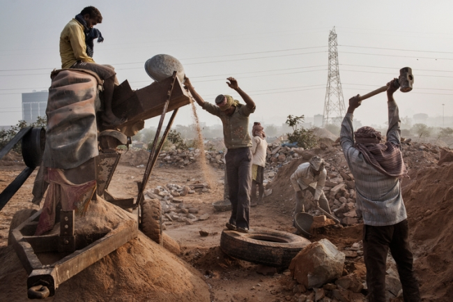 Indian workers crush stone into sand at an Illegal mine near Raipur Village in Greater Noida, Uttar Pradesh, India on March 18, 2013. The mine was opposed by Raipur local Pale Ram Chauhan, who was murdered in his home after speaking out against local powerbrokers controlling the sand trade. As construction and industry drive a demand for sand, illegal sand mining is stripping riverbeds and beaches of sand with severe environmental consequences. The unregulated sand mining industry employs thousands of workers who depend on the mining for their livelihood and is controlled by local powerbrokers. Photo by Adam Ferguson for WIRED
