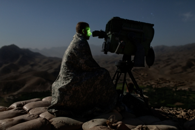 A U.S. Army soldier from 3rd Platoon, Apache Company, 2nd Battalion, 87th Infantry Regiment, 3rd Brigade Combat team, 10th Mountain Division, surveys a road with a Long Range Acquisition Sight, on an observation post in the Tangi Valley, Wardak Province, Afghanistan, on September 4, 2009. Photo by Adam Ferguson