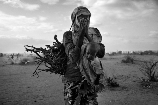 A refugee women from Somalia carries sticks and a baby in a new area of Dadaab refugee camp, North Eastern Province, Kenya on Aug. 4, 2011. Photo by Adam Ferguson