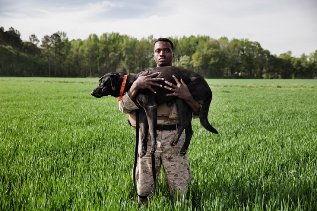 Marine Corporal Dashno Villard and Improvised Detection Dog Bank stand for a portrait during a K2 Solutionstraining course in Ellerbe, North Carolina, U.S. on April 18, 2013. Marines undertake a 5-week K2 training course to become IDD handlers before returning to their respective Marine Company and deploying to Afghanistan. Photo by Adam Ferguson for National Geographic